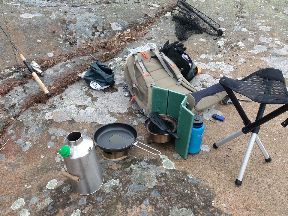 Fishing trip (Sweden). Using hobostove with alcohol burner to make pancakes, and boiling water with Kelly Kettle for coffee and warm dishing water. Pine cones a few feet away as fuel