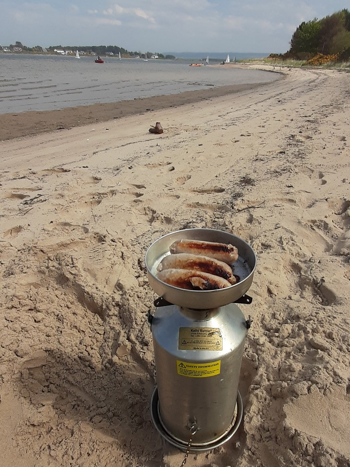 Sausages in the sun thanks to our Kelly Kettle. (Findhorn Bay, Scotland)