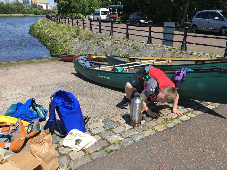One of our young people making a brew after a hard days paddle with a Kelly Kettle on the River Lagan in Belfast, Northern Ireland